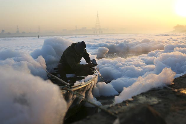 An Indian man bails water from his boat while surrounded by polluted foam in New  Delhi at dawn on Dec. 9, 2012. Photograph by Andrew Caballero-Reynolds/AFP via Getty images