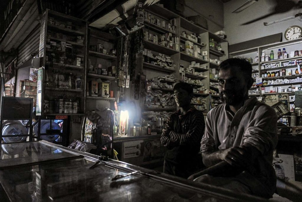 Pakistani vendors wait for customers in a dark shop during a power cut in Islamabad. India may lay claim to the largest blackout in history, but an endemic energy crisis blamed on years of mismanagement in Pakistan cripples the economy and makes millions of lives a daily misery. Photo: Aamir Qureshi/AFP/GettyImages