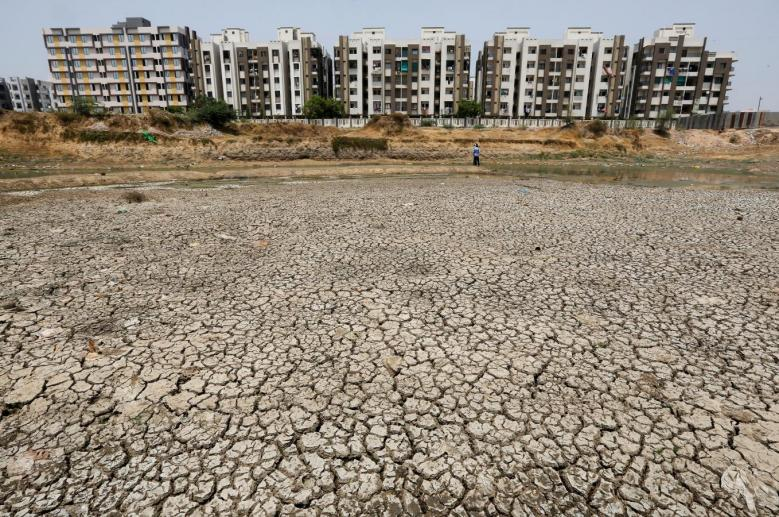 Residential apartments are seen next to the dried-up Ratanpura lake on the outskirts of Ahmedabad. REUTERS/Amit Dave