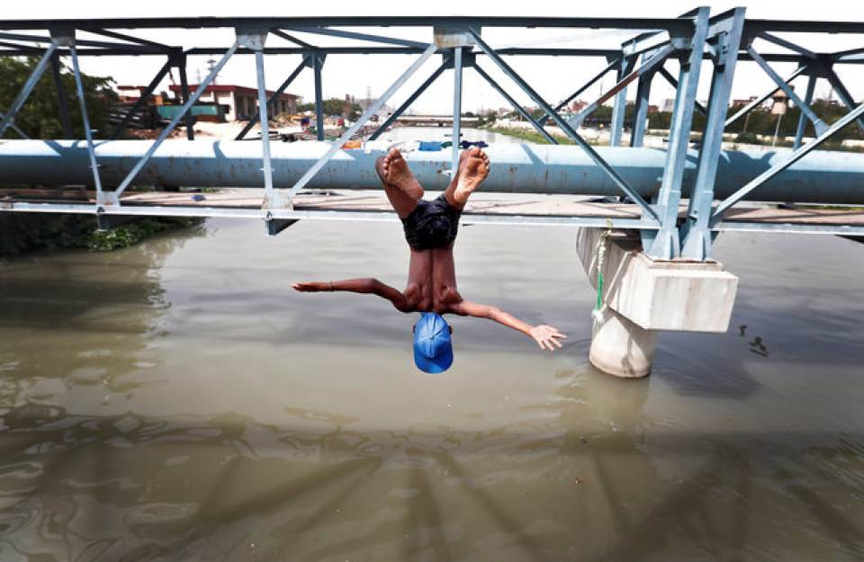 A boy jumps from a water pipe into a canal as temperatures soar in New Delhi. Access to clean and regular water remains a challenge for India's capital. Cathal McNaughton/Reuters